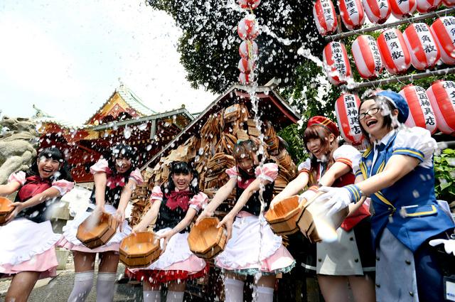 神田明神の境内で打ち水をするメイドカフェの店員たち=14日午前、東京都千代田区、北村玲奈撮影