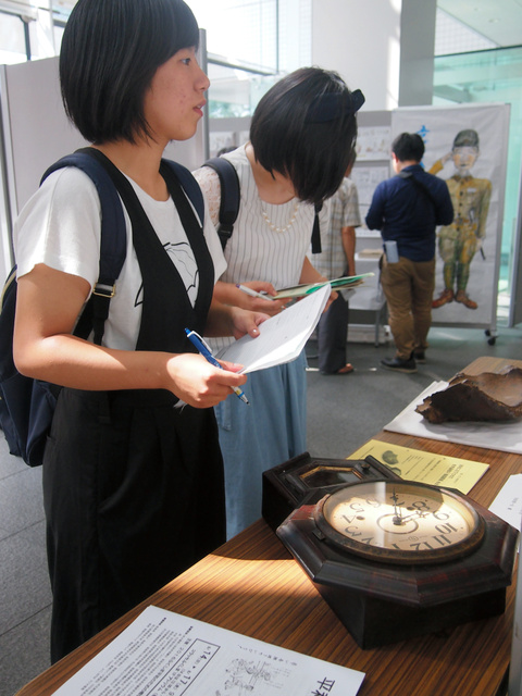 福島市渡利に投下された爆弾の破片や当時の時計を見つめる高校生=福島市のコラッセふくしま
