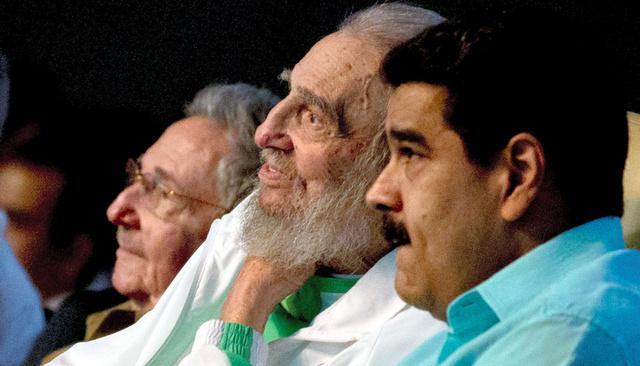 ベネズエラのマドゥロ大統領(右)に話しかけるフィデル・カストロ前国家評議会議長(中央)。左は弟のラウル・カストロ議長。キューバ政府系メディア「クバデバテ」が掲載した=ロイター