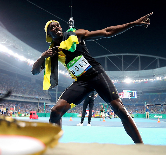 100メートルで3連覇を果たし、金色の靴(左下)を置き、ポーズを決めるボルト=14日、長島一浩撮影
