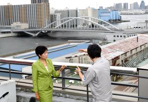 築地市場を視察する小池百合子知事。奥は新橋と豊洲をつなぐ環状2号線の「築地大橋」=16日午後、東京都中央区、北村玲奈撮影