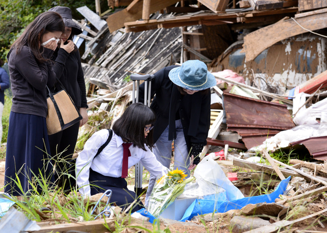 熊本地震の本震発生後に亡くなった片島信夫さん(当時69)、利栄子さん(同61)夫婦の自宅前に花を供える遺族たち=16日午前10時37分、熊本県南阿蘇村、福岡亜純撮影