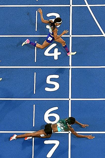 女子400メートル決勝、1位でゴールするミラー(下)と2位のフェリックス=AFP時事