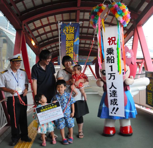 今季の桜島納涼観光船の乗船1万人目となった西小野航君(中央)と家族=鹿児島市