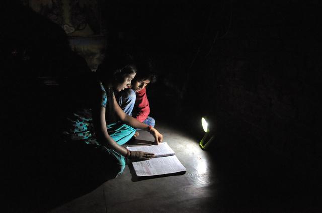 昼間に充電したソーラーランタンで本を読むポージャさんとアカシュ君のきょうだい=5月、インド北部のウッタルプラデシュ州ゴート村