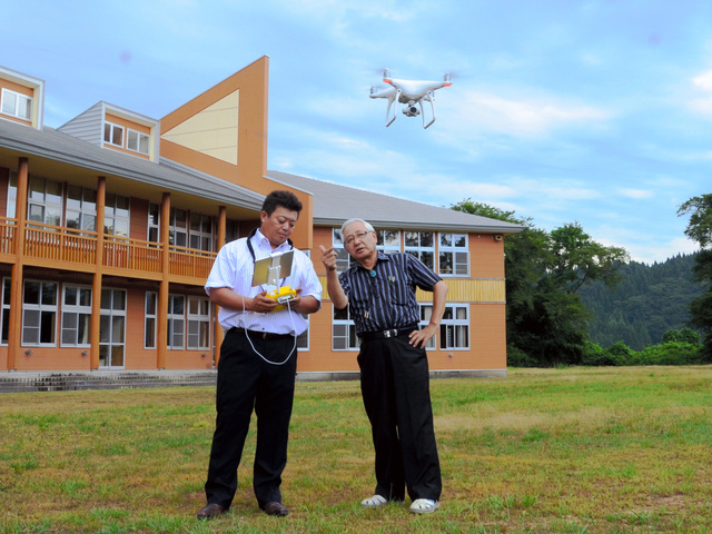 旧馬場目小の校庭でドローンの試験飛行をする佐藤茂幸さん(左)と伊藤驍校長=五城目町馬場目