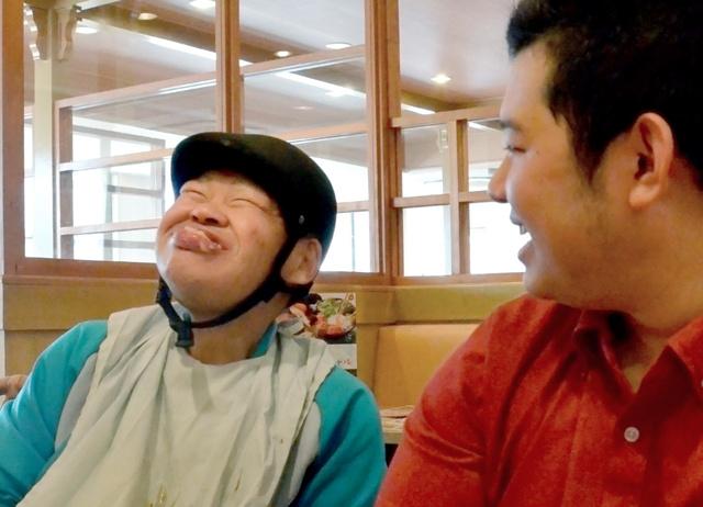 外出先のファミリーレストランでポテトを口いっぱいにほおばり、笑顔を見せる正木祐治さん(左)=広島県東広島市