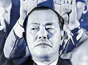 自民党総裁になった田中角栄氏。後ろで派閥議員が壇上の選挙管理委員にサインを送る=1972年7月5日、東京都