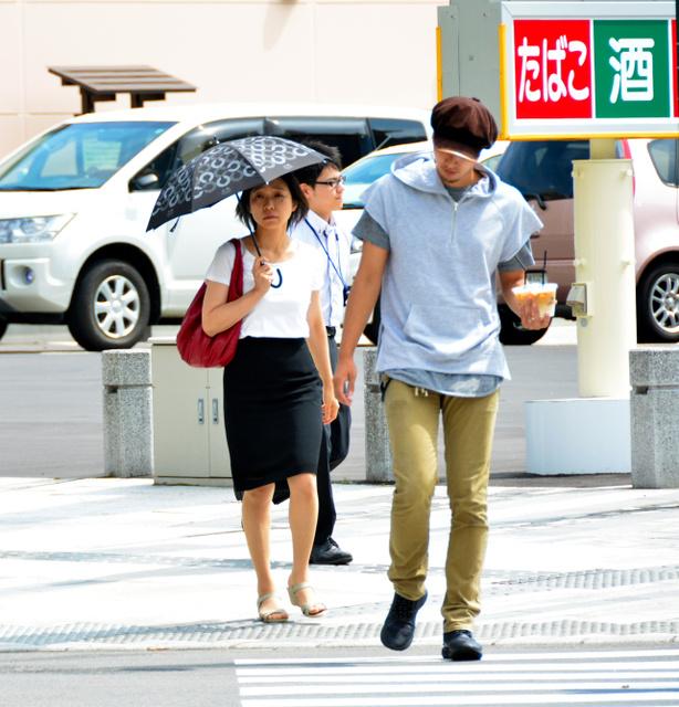 強い日差しに、日傘をさしたり冷たい飲み物を買い求めたりする人もいた=19日、青森市新町2丁目