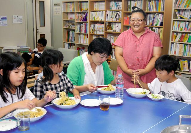 100回目を調理した小松美香さん(右から2人目)と子ども食堂の利用者ら=舞鶴市市場