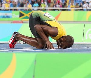 男子200メートルで3連覇を達成し、フィニッシュラインにキスするボルト=西畑志朗撮影