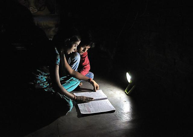 ソーラーランタンで本を読むポージャさんとアカシュ君のきょうだい=5月、インド北部のウッタルプラデシュ州ゴート村