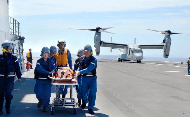 鹿児島県沖で行われた米軍オスプレイの海自護衛艦への発着訓練。搬送されてきた負傷者を海自隊員が運んだ=7月22日、護衛艦いずも
