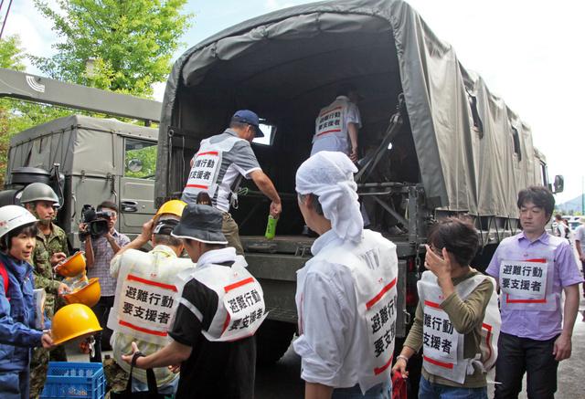 自衛隊のトラックで隣町の避難所へ移動する富士吉田市民=富士吉田市緑ケ丘2丁目