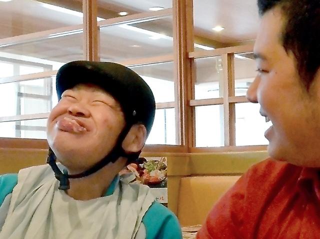 外出先のファミリーレストランでポテトを口いっぱいにほおばり、笑顔を見せる正木祐治さん(左)