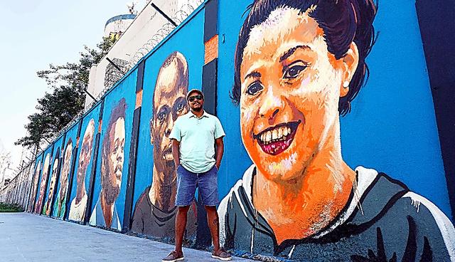 壁画の前に立つロドリゴ・シニさん。手前の絵は、シリア出身の競泳選手ユスラ・マルディニ=ブラジル・リオデジャネイロ