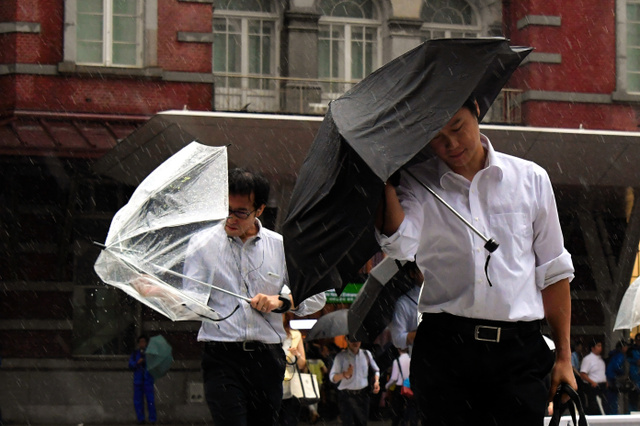 台風9号の接近で時折吹く強風の中、通勤する人たち=22日午前、東京都千代田区、小玉重隆撮影