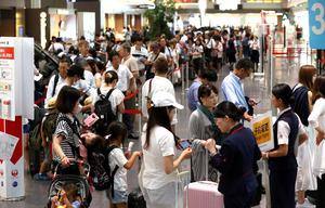台風の影響で欠航が相次ぎ、航空会社の窓口にはキャンセルや変更の手続きのため、長い列ができていた=22日午前9時9分、羽田空港、嶋田達也撮影