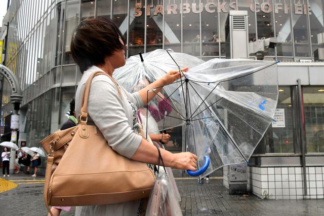 強い風に傘が飛ばされそうになりながら、東京・渋谷のスクランブル交差点付近を歩く人たち=22日午後、東京都渋谷区、小玉重隆撮影