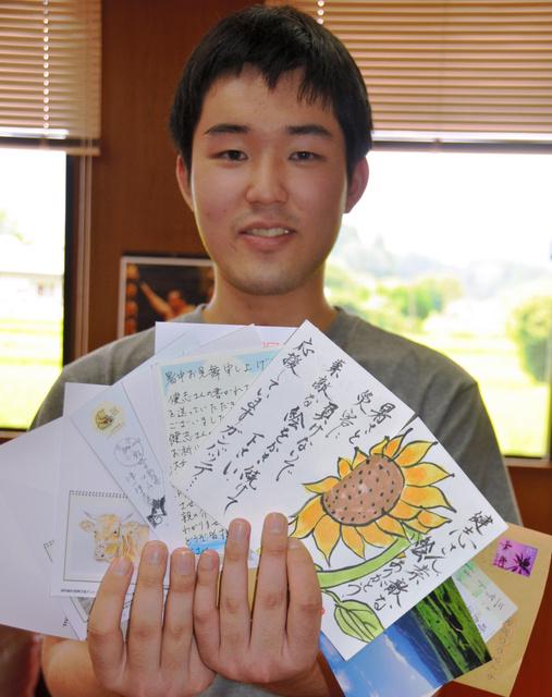 ポストカードを買った人たちから届いた激励の便りを持つ相戸健志さん=熊本県南阿蘇村役場