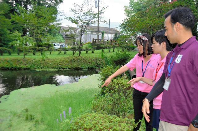 地震後に湧いた水を見て驚く台湾人学生=阿蘇市の産神社