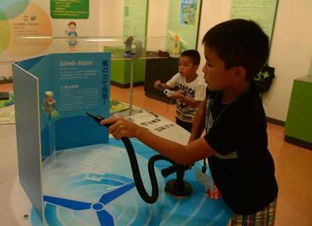 ポンプを押して風力を生む仕組みを体験する児童