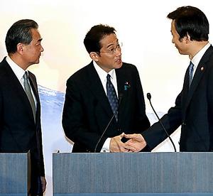 共同記者発表を終え、握手する(右から)韓国の尹炳世外相と岸田文雄外相。左は中国の王毅外相=24日、岩下毅撮影