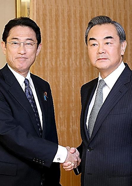 外相会談前に握手する岸田文雄外相(左)と中国の王毅外相=24日午後3時30分、代表撮影