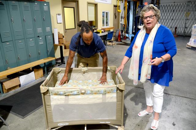 低所得世帯向けに格安で提供されるベビーベッド。活動を担うジュディス・バノンさん(右)は「5分もかからず組み立てられます」=2日、米ペンシルベニア州ピッツバーグ