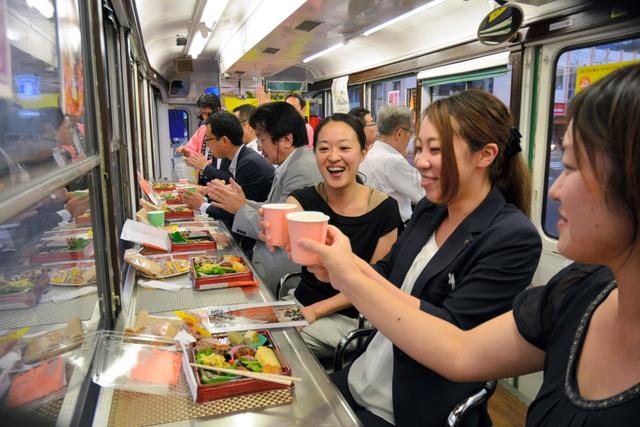 「さつま焼酎電車」の車内で、焼酎で乾杯する乗客たち=鹿児島市