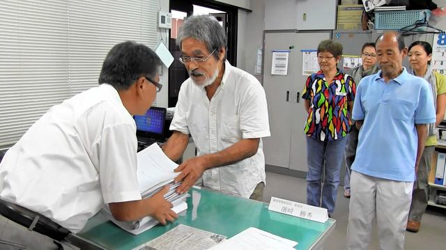 町選管に署名簿を提出する「屋久島の未来を考える会」の松田正代表(中央)ら=屋久島町