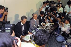 """大手メーカーや商社などの損失補<Asajikai sjis=""""填"""">塡</Asajikai>の相手先リストが大蔵省の要請で大手証券4社から公表された。4社分をまとめたリスト公開の記者会見に臨む関要日本証券業協会専務理事(中央)=1991年7月29日"""