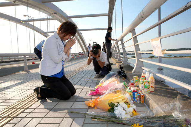 幼い子ども3人が亡くなった海の中道大橋で、自身も飲酒運転事故で長男を失った山本美也子さんが手を合わせた=25日午後5時9分、福岡市東区、河合真人撮影