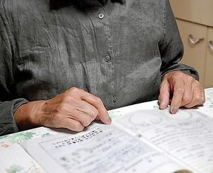 強制不妊手術を受けたと訴える女性。「優生手術の必要を認められる」と書かれた、宮城県の相談所の書類を前に(画像の一部を加工しています)