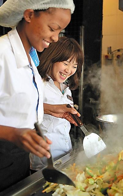 ケニア人スタッフに「野菜炒め」の作り方を教える村原圭子さん=ナイロビ、三浦英之撮影