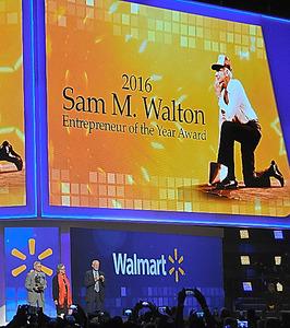 スクリーンに映し出された故サム・ウォルトン。壇上には右から長男、長女、三男=6月、米アーカンソー州