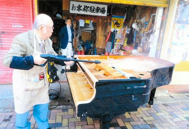 高圧水で被災ピアノを洗う井上晃雄さん=5月18日、本人提供
