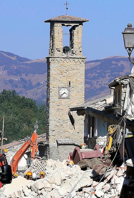 イタリア中部のアマトリーチェで25日、倒壊した建物の中に立つ鐘楼=AP。時計の針は地震が起きた時刻で止まっていた