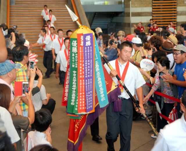 優勝報告会を終え、深紅の大優勝旗を手に退場する選手たちに温かい拍手が送られた=県庁