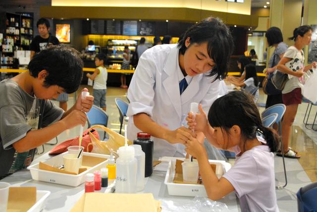 錦江湾高の生徒に手ほどきを受けながら実験する子どもたち=鹿児島市東開町