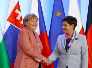 ワルシャワで26日、ポーランドのシドゥウォ首相と握手をするメルケル首相(左)=ロイター