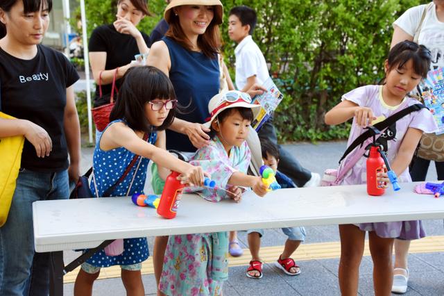 消火器を模した水鉄砲で的をねらう子どもたち=神戸市中央区