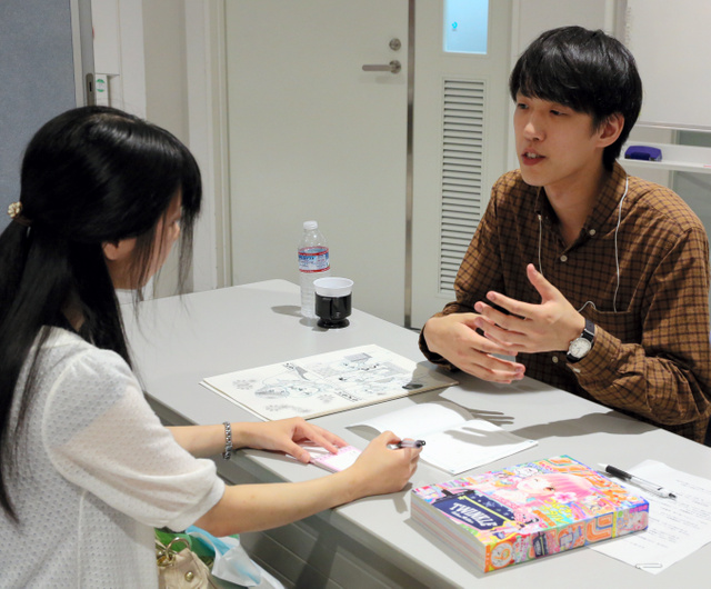 編集者(右)に持ち込んだ原稿を見せながら助言を受ける参加者=北九州市小倉北区の市漫画ミュージアム
