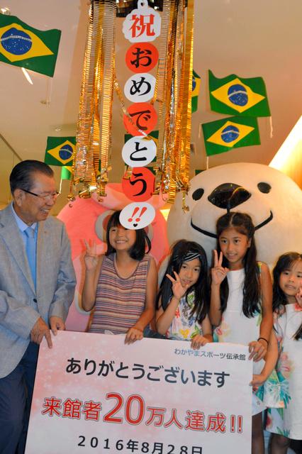 来館者20万人を突破し、記念品を受け取った子どもたち=和歌山市本町2丁目