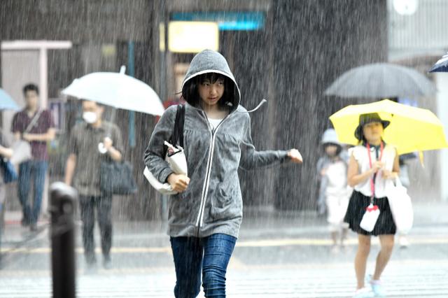 土砂降りの中、横断歩道を走って渡る人の姿が見られた=28日午後1時27分、福岡市博多区、福岡亜純撮影