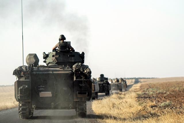 トルコ南部で27日、シリア国境に向かうトルコ軍。過激派組織「イスラム国」(IS)から拠点を取り戻し、シリアのクルド人勢力を封じ込めるため、トルコは24日、シリアに軍を派遣した=AP