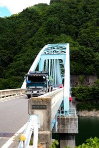 南アルプストンネルの残土搬送路に予定している県道松川インター大鹿線の四徳大橋。道路改良の一環で橋の奥にトンネルが新設される=中川村
