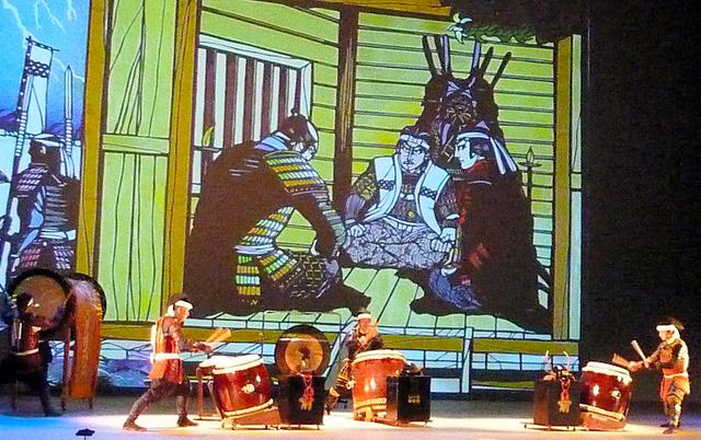 イラストを背景に「犬伏の別れ」を奏でる保存会のメンバー=昨年12月、長野県上田市、信州上田真田陣太鼓保存会提供