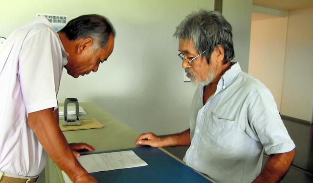 パブリックコメントを集めることを求める陳情書を町議会事務局に提出する松田正代表(右)=屋久島町