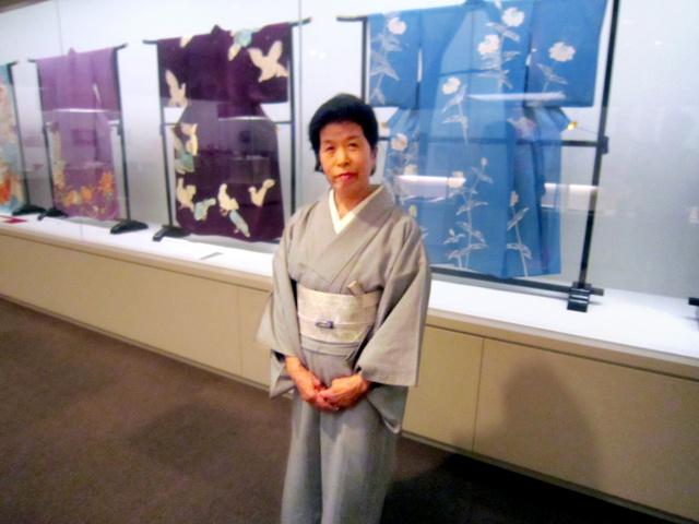 母の着物の前に立つ佐野恵美子さん